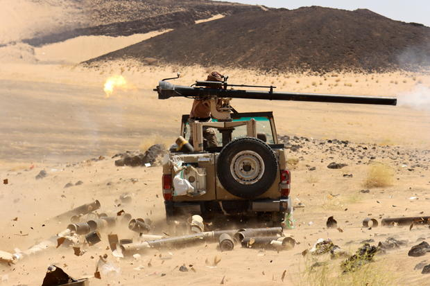 Yemeni government fighter fires a vehicle-mounted weapon at a frontline position during fighting against Houthi fighters in Marib