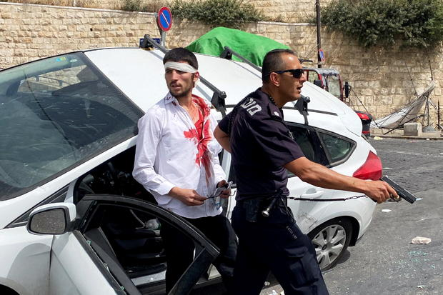 An Israeli police officer holds his weapon as he stands in front of an injured Israeli driver moments after witnesses said his car crashed into a Palestinian on a pavement during stone-throwing clashes near Lion's Gate just outside Jerusalem's Old City
