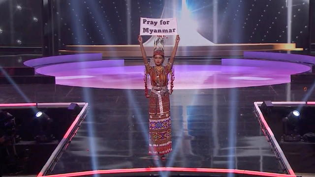 "Ma Thuzar Wint Lwin, Miss Universe Myanmar, holds the ""Pray for Myanmar"" sign during Miss Universe pageant's national costume show, in Hollywood"