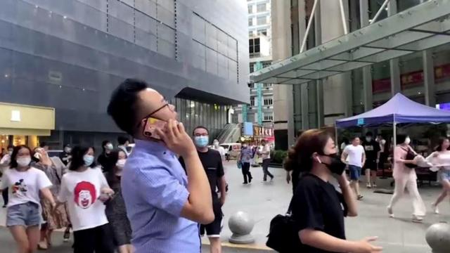 People gather outside the 73-storey SEG skyscraper in Shenzhen