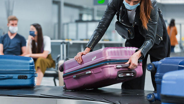 Airplane traveler wearing N95 face mask receiving luggage from conveyor belt
