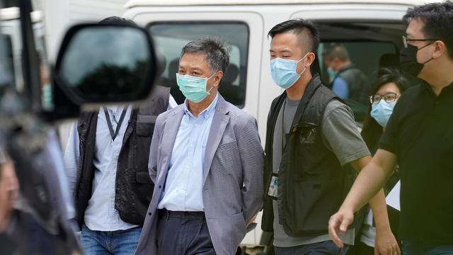 Police officers from the national security department escort Chief Operating Officer Chow Tat-kuen from the offices of Apple Daily and Next Media in Hong Kong