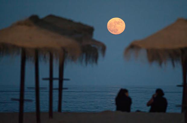 The full super moon rising over Malagueta beach.According