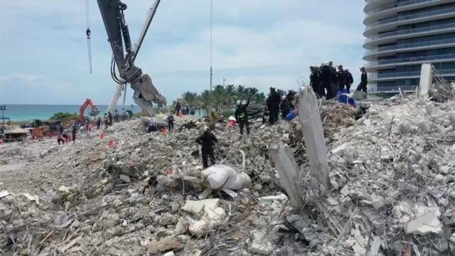 Search-and-rescue crew personnel on the debris of the collapsed Champlain Towers South condominium in Surfside, Florida