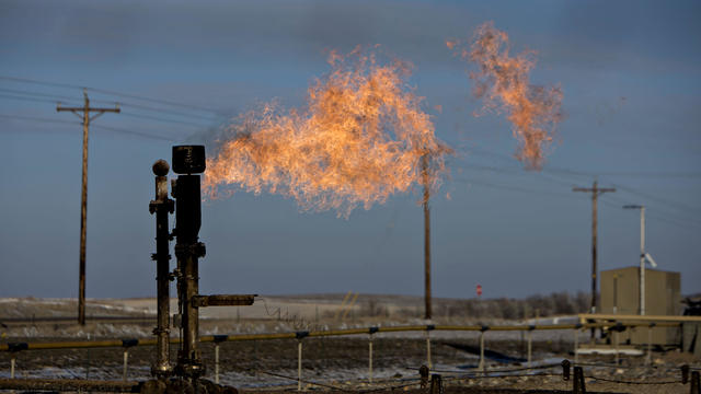 Gas flare burns against blue sky