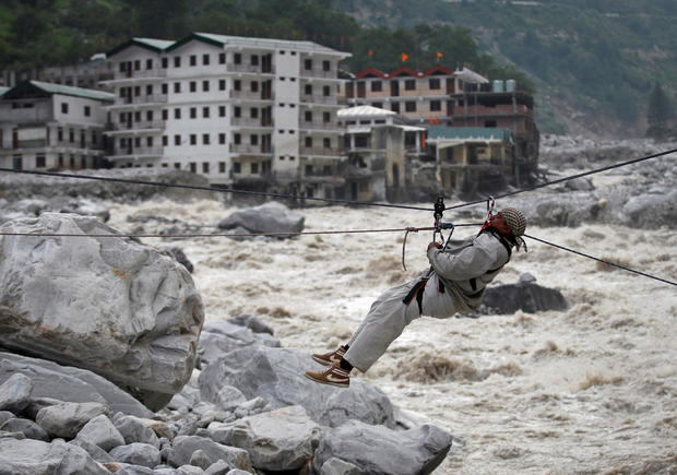 FILE PHOTO: A man is pulled across to safety on a rope during rescue operation in Govindghat