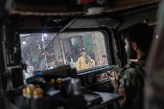 People watch as the convoy of Afghan Special Forces passes through a market during a combat mission against Taliban, in Kandahar province