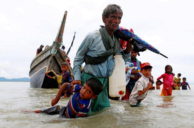 FILE PHOTO: A Rohingya refugee man pulls a child as they walk to the shore after crossing the Bangladesh-Myanmar border by boat through the Bay of Bengal in Shah Porir Dwip