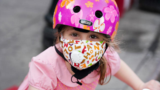 A child wearing a protective mask waits outside Lenox Hill Hospital to show gratitude to the medical staff during the coronavirus pandemic on May 15, 2020, in New York City.