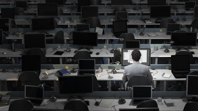 An office worker sits working in an empty office