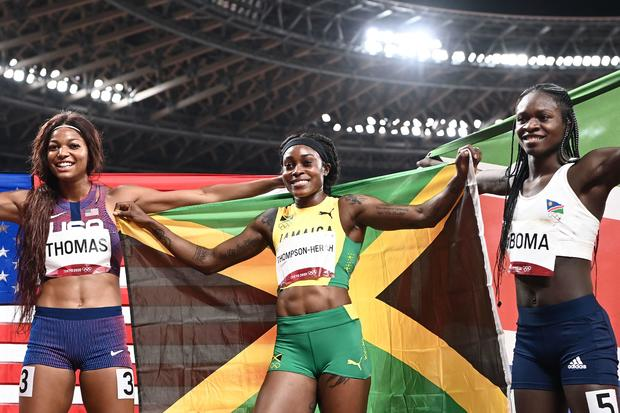 Gold medalist Jamaica's Elaine Thompson-Herah, center, silver medalist Namibia's Christine Mboma, right, and bronze medalist USA's Gabrielle Thomas pose after the women's 200-meter final during the Tokyo Olympic Games at the Olympic Stadium in Tokyo on August 3, 2021.