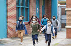 School children with face masks running outside building