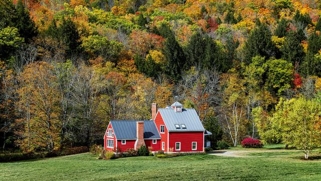 Charming red house flanked by autumn foliage in Vermont.