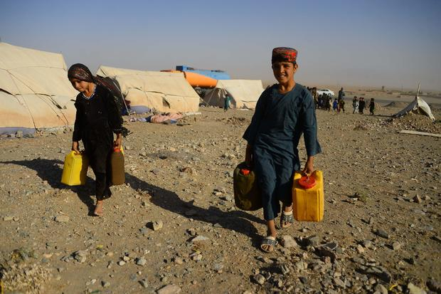 Afghan children carry water containers