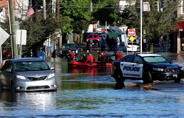 First responders pull residents in a boat following flooding in Mamaroneck, New York