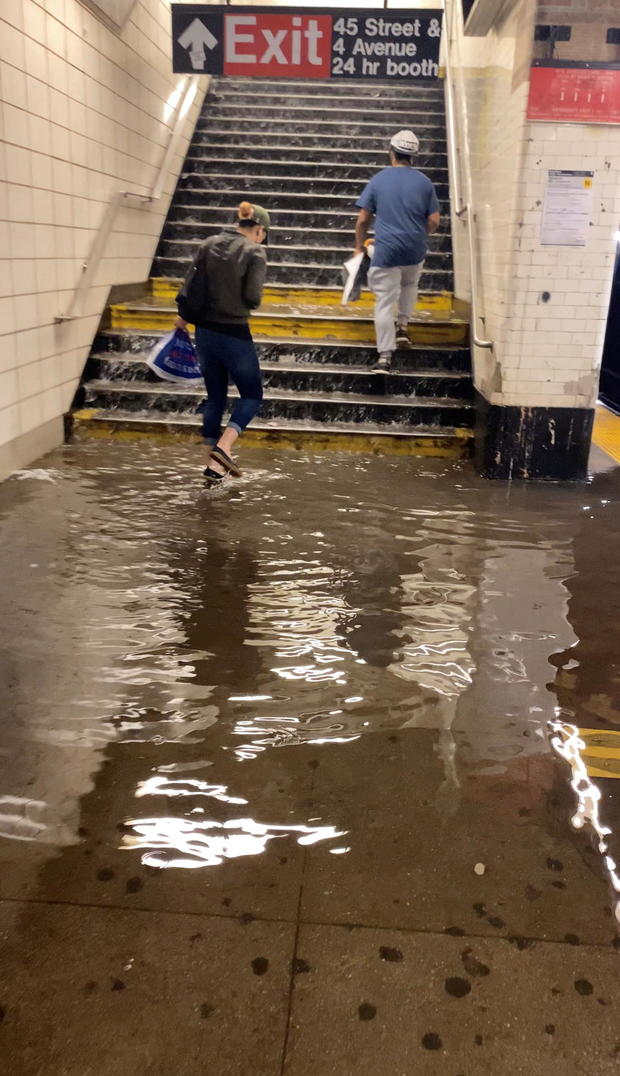 New Yorkers walk through flooded subway station