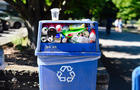 Blue plastic recycling bin full of bottles and cans