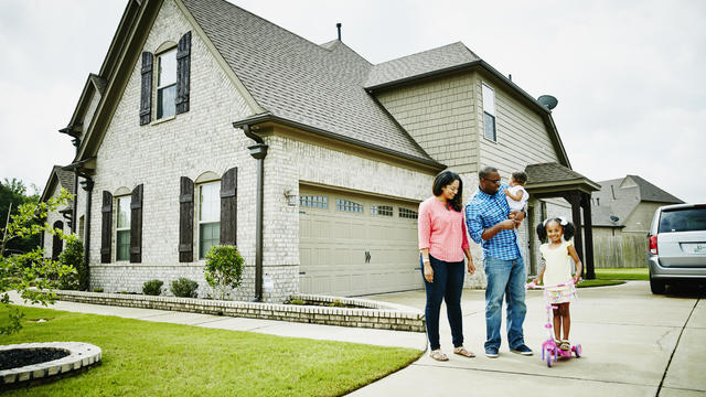 Portrait of family in driveway in front of home