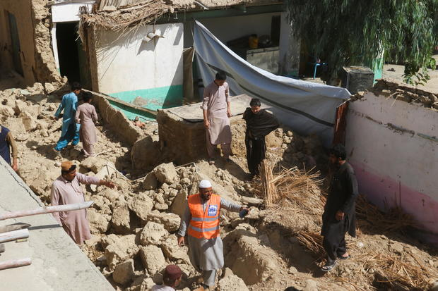 Rescue worker and residents stand amid the rubble of a damaged house following an earthquake in Harnai