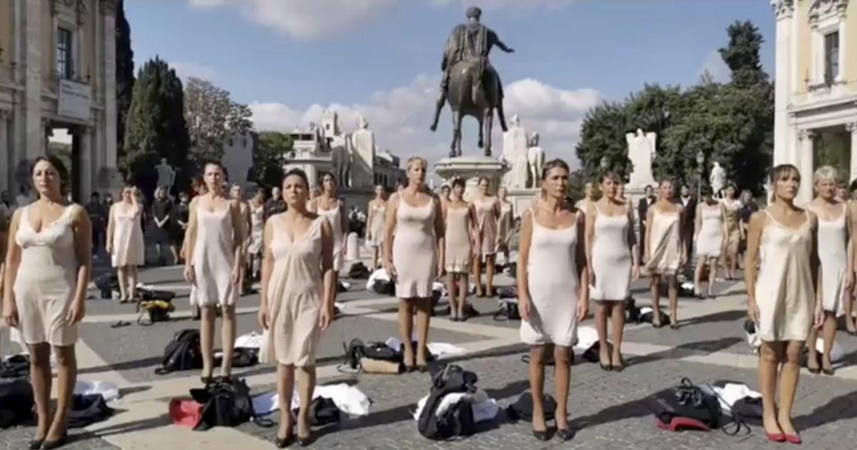 Dozens of former Alitalia flight attendants strip off uniforms in protest