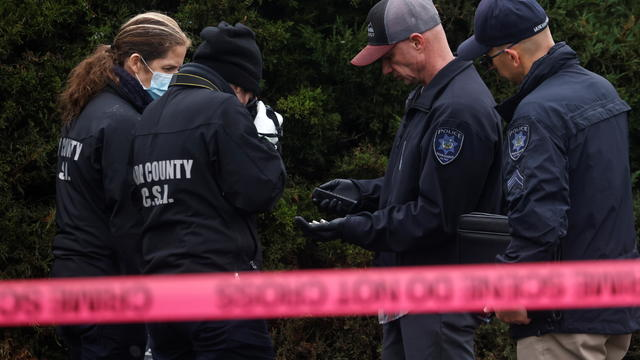 Law enforcement officers collect evidence near the scene of a shooting at the Boise Towne Square shopping mall in Boise, Idaho